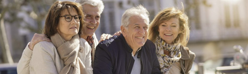 Group of senior people on vacation leaning on fence
