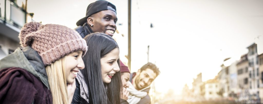 Group of multi-ethnic friends walking on the streets and smiling - Young people having fun outdoors team building activity.
